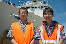 Two scientists, Tokyo University's Dr Masato Moteki and Australian Antarctic Division's Dr So Kawaguchi, on the dock next to the Japanese ship the Umitaka Maru