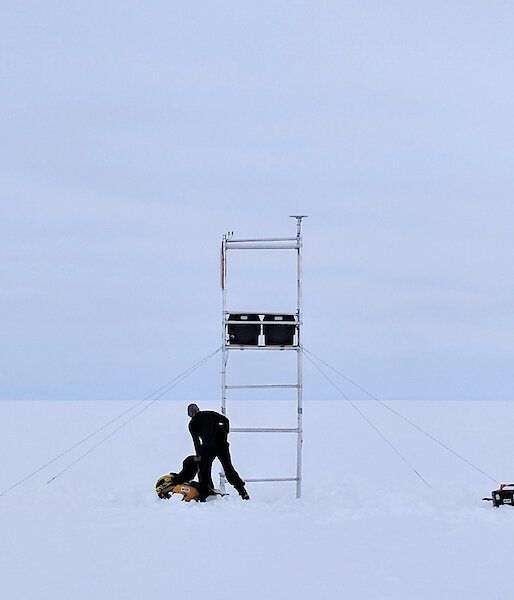 Two sillhouettes of people with instruments on scaffolding on a glacier