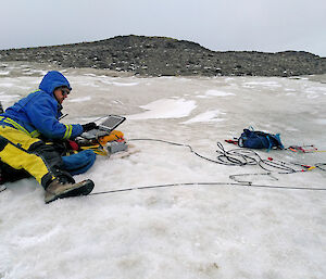 Scientist sitting on ice-covered rocks with a laptop to monitor seismic tests.