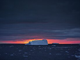 An iceberg against a pink sunset.