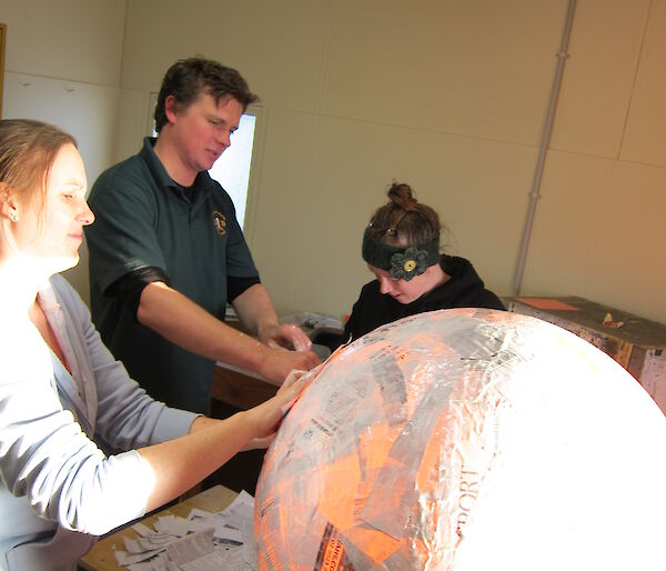 The beginning of the piñata with people and a ball of papier mache
