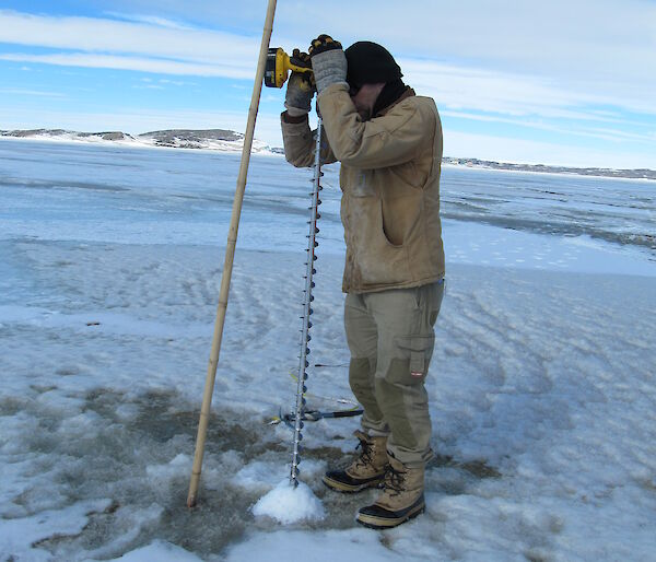 Adam Christensen drilling the sea ice