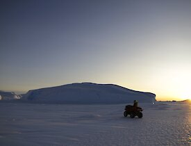 A large ice berg stuck in the fast ice in the distance with a quad bike and rider in the foreground