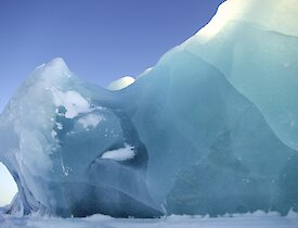 The sun brings out the beauty of the ice bergs stuck fast for the winter in the frozen sea ice