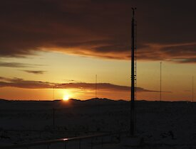 The sun rises above the horizon in clear skies with the weather station mast, antenna masts and cloud cover in the foreground