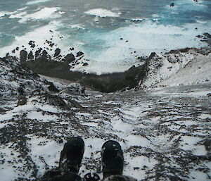 Expeditioner points camera at feet dangling over any icy cliff on Macquarie Island