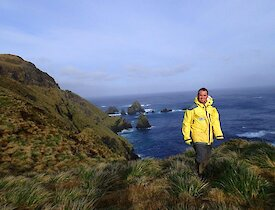 Josh standing amongst the tussock with the steep rugged slopes of the escarpment in the background. There are also some impressive large pointy rock stacks in the ocean just offshore