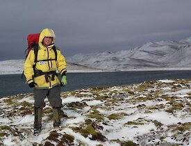 Josh, in all his cold weather gear and carrying his survival pack, standing on the snow covered track. Behind him is a lake and snow covered hills beyond