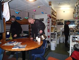 Inside Hurd Point hut — shows ranger Chris working in the kitchen, while Craig can be seen pouring water from a kettle into a mug on the oval table. Clive is standing behind the table