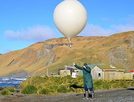Craig, dressed in all the protective safety clothes, including goggles and gloves, releasing the large weather balloon with a ozone sonde attached. It is a bright sunny morning, highlighting the colours of the escarpment in the background