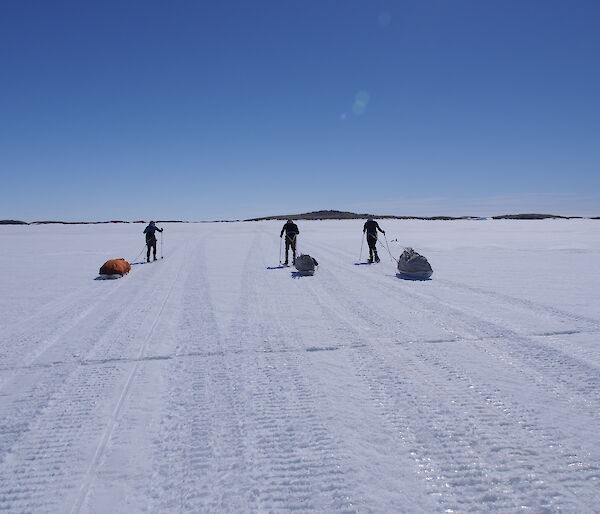 Three expeditioners pulling sleds of gear on the sea ice across to an island