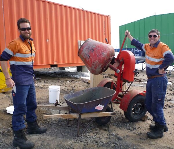 Two expeditioners standing beside a cement mixer and wheel barrow