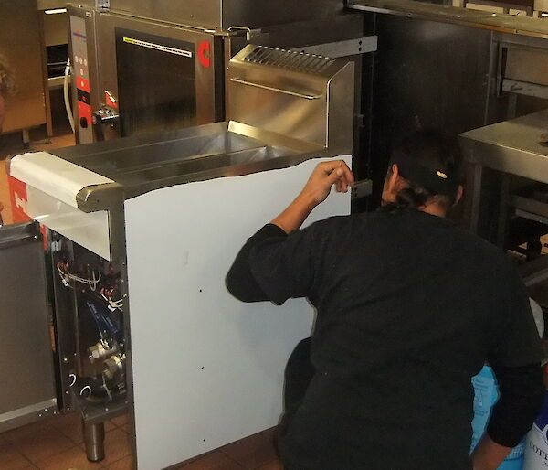 Two expeditioners installing large industrial kitchen equipment