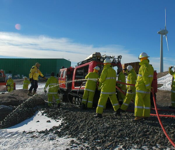 Mawson fire exercise showing a fire truck and expeditioners if firefighting uniforms during the training