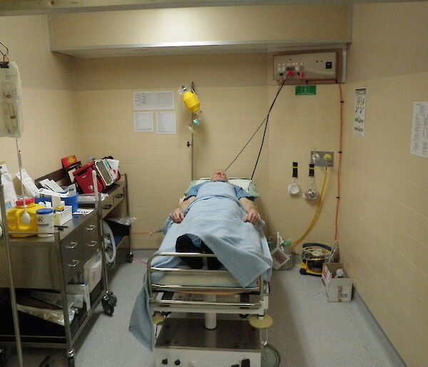 Medical training — a man lies in a hospital bed pretending to be a patient waiting for surgery