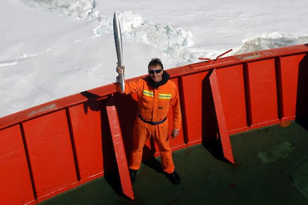 Expeditioner standing on the deck of the ship, holding the Queen's Baton