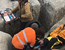 Expeditioners use a first aid kit to assist the patient