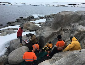 Expeditioners provide first aid to the patient during the SAR exercise