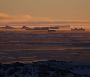 Distant icebergs on the far horizen lit up with orange and purple light at sunrise, steam fog coming from areas of open water, sea ice forming in the closer water and foreground is rocky ground