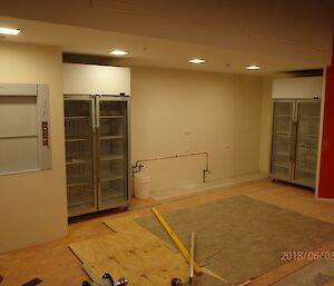 Back end of large room showing L to R: dumb waiter lift doors, double doored fridge, blank wall for servery area, 2nd double doored fridge, and partial wall with rough orange paint. Floor infront is pale orange lino with work tools scattered across