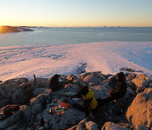 Men sitting around a cheese platter on rocky outcrop in foreground, in background is a stretch of sea ice then open water with the sun setting