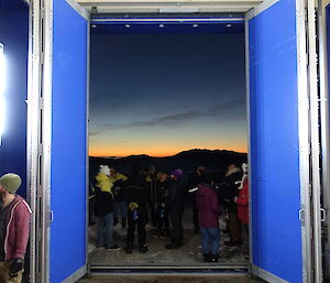 Photo taken from inside blue building with double width and heigh doors opened inwards and group of people gathered outside. In the distance the sun is setting over hills sillouhetted against night sky