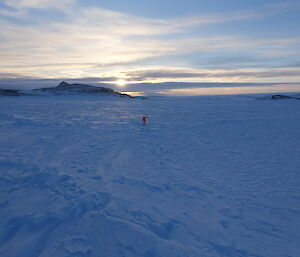 Person if fluro orange dry suit in middle of sea ice channel between Bailey Peninsula and Shirley Island, in distance rocky outcrops of island and sun is low on horizen lighting the cirrostratus cloud across the sky