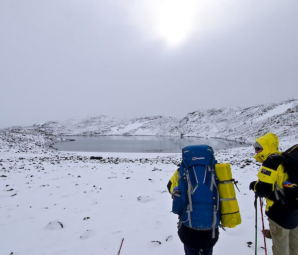 Two expeditioners walking towards a lake