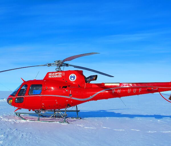 Red helicopter in foreground. Scientific instruments on ice shelf in background