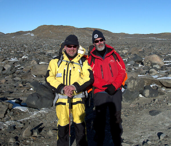 Two expeditioners, rocky terrain in background pose for photograph