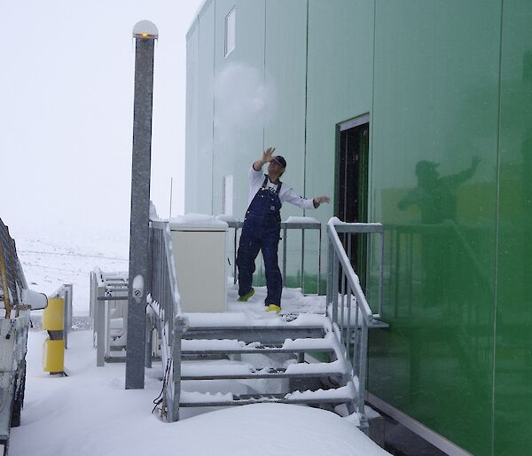 Expeditioner throwing a snowball from off the back of the living quarters
