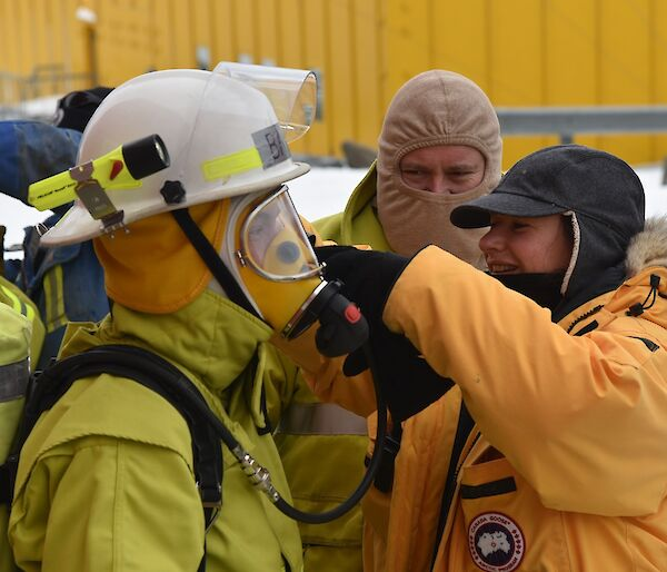 Expeditioner assists another with breathing apparatus during a fire drill