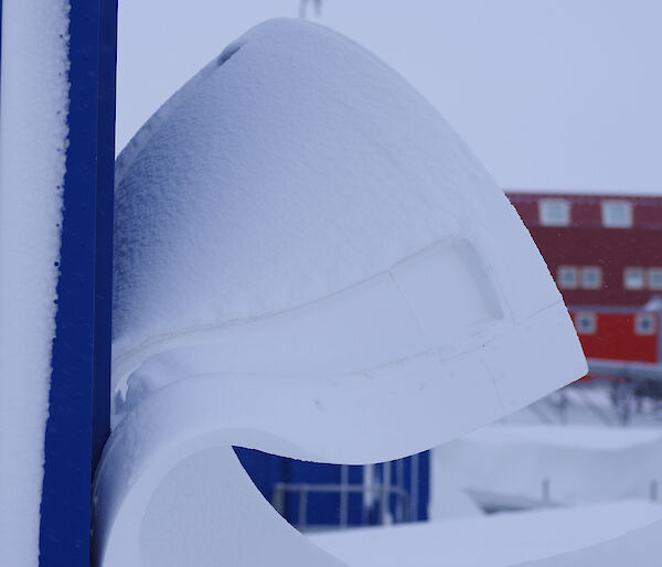 A large wave of snow leeping off an outlying power building on station