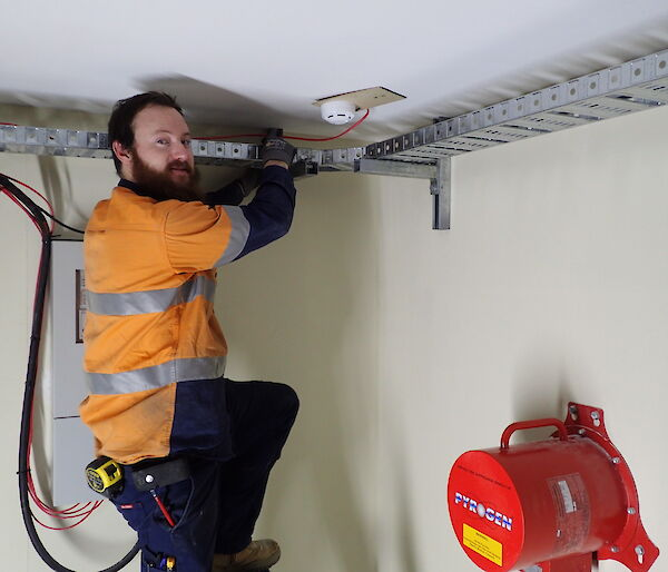 Expeditioner standing on a ladder inside a ring main unit