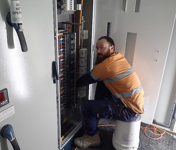 Expeditioner seated on a white bucket facing an electronics control board