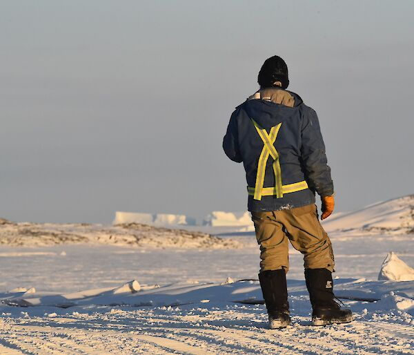 Expeditioner standing back to camera with sea ice in background