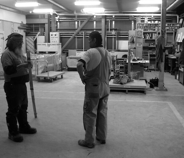 Two expeditioners standing in an empty storehouse