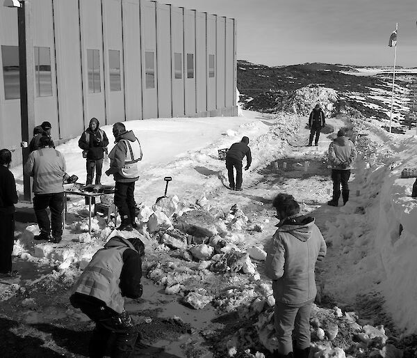 Expeditioners gathered outside a building playing games and talking