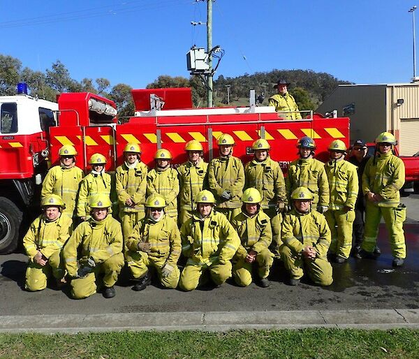 Large group of people in fire fighting gear pose together in front of a fire truck