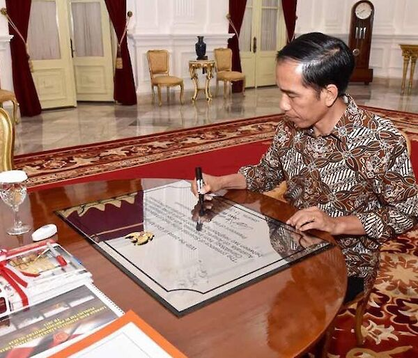 The Indonesian President siting at a desk signing a plaque