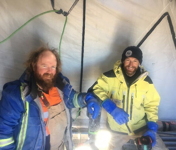 Two men stand in a tent with a drill.