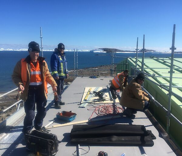 4 men repair a roof with icebergs in the distance