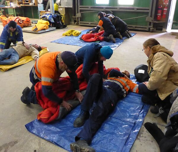 Expeditioners in groups of 3 with a patient who is acting out an injury is rolled into a sleeping bag and onto a blue matt.