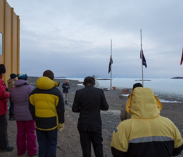 Expeditioners conducting the Anzac dawn service at the station flagpoles with the Australian, aboriginal and New Zealand flags at half-mast.