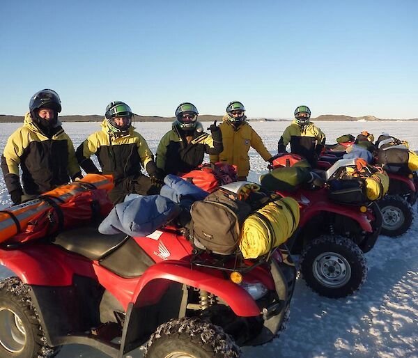 A Line up of Quad bikes with expeditioners standing behind them on the sea ice under clear blue skies.