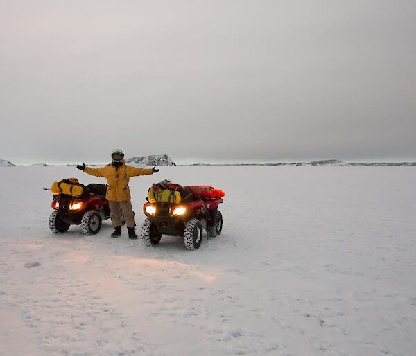 Daniel standing with two Quad bikes before sunrise on the sea ice with shore in the distance