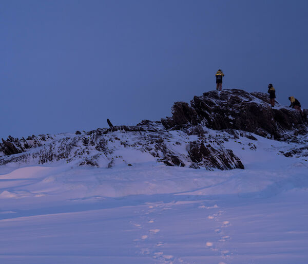 Three expeditioners standing on top a small rocky hill which is surrounded by sea ice and snow.