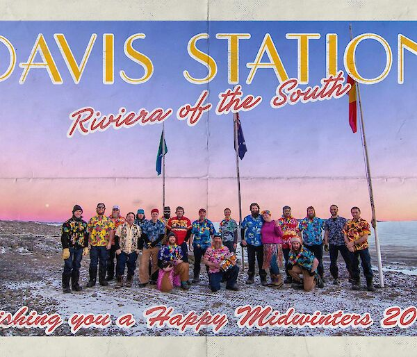 Group photo of station expeditioners all wearing Hawaiian shirts under the flag poles on a blue sky day with a red sun haze on the horizon.
