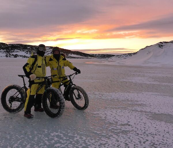 Jason and Graham stopping to pose for a photo with their bikes on the sea ice with a sunset as the backdrop.
