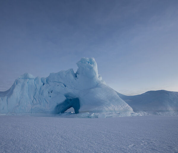 An ice burg locked in the sea ice that has a large hole weathered in the side.
